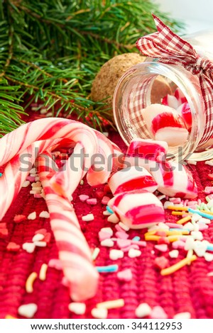 Sweet striped candy canes spilled/poured from glass jar. Green fir on red christmas background. Multicolored indoors vertical close-up image. - stock photo