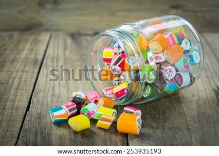 Sweet sugar candies in glass jars on wooden background - stock photo
