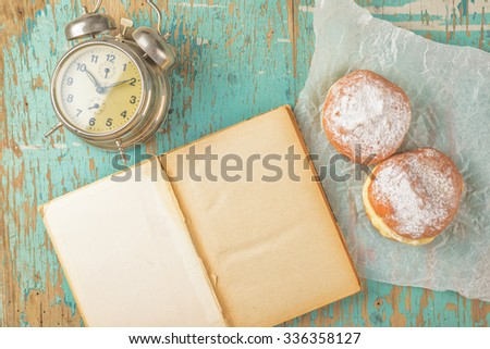 Sweet sugary donuts, old book and vintage alarm clock on rustic wooden kitchen table, top view of tasty bakery doughnuts in vintage retro toned overhead shot - stock photo