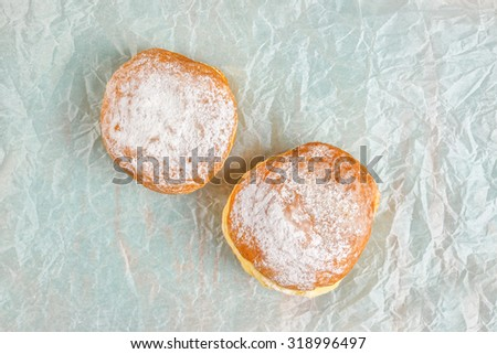 Sweet sugary donuts on crumpled baking paper, top view of tasty bakery doughnuts in vintage retro toned overhead shot - stock photo