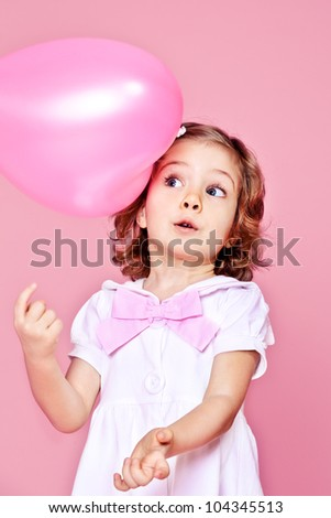 Sweet surprised girl playing with pink balloon - stock photo