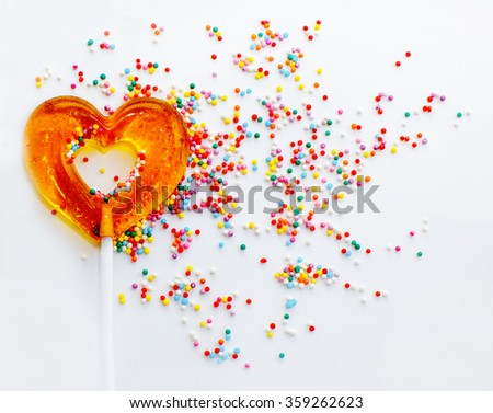 sweet symbol of love. lollipop in a heart shape on the background of colorful sprinkles - stock photo