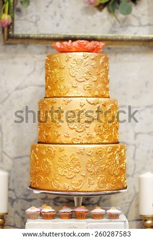 Sweet table with big golden cake  - stock photo