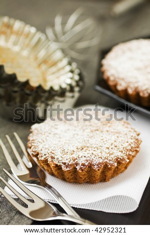 Sweet tart with sugar and some kitchen utensils - stock photo