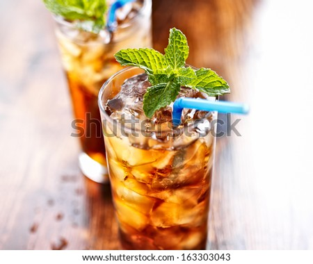 sweet tea with ice and blue straw - stock photo