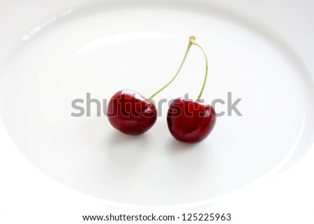 Sweet temptation: two lush cherries on a white plate. - stock photo