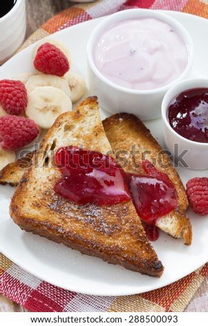 sweet toasts with fresh raspberry, jam and yoghurt for breakfast, close-up, vertical, top view - stock photo