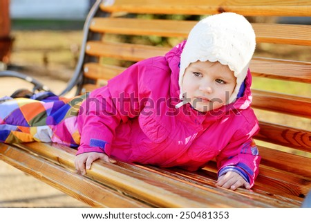 sweet toddler girl is laying on the bench - stock photo
