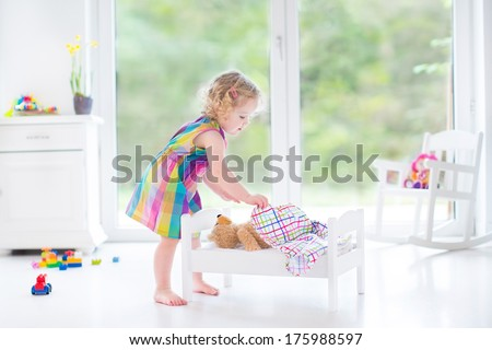 Sweet toddler girl playing with her teddy bear in a sunny room with big garden view windows - stock photo