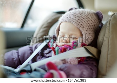 Sweet toddler girl sleeping peacefully in a car seat at winter - stock photo