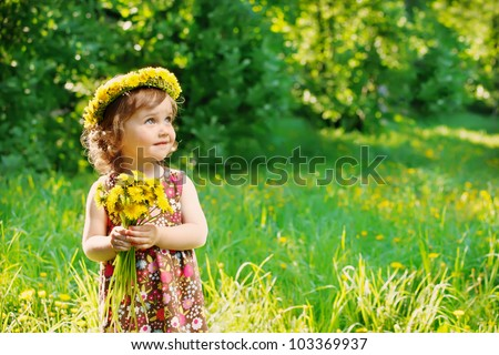Sweet toddler girl with floral head wreath on and flowers bunch in hands - stock photo