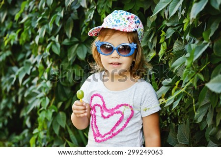 sweet toddler girl with lollipop and sun glasses - stock photo