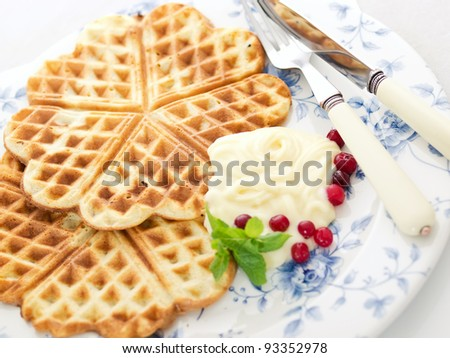 sweet wafer hearts on dish with cream, berries and mint - stock photo