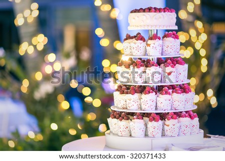 Sweet wedding cake made from fresh berry cupcake with bokeh background. - stock photo