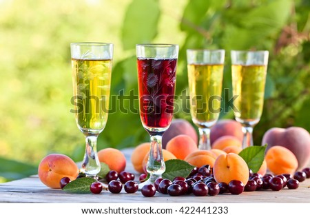 Sweet wine with apricots and cherries on  wooden table - stock photo