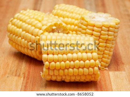 Sweet yellow corn cobs on a wooden chopping board - stock photo