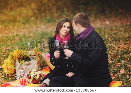 Sweet young couple drinking vine outside, talking - stock photo