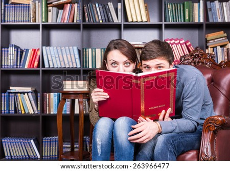 Sweet Young Couple Sitting at the Library While Hiding Behind a Red Book and Looking at the Camera. - stock photo