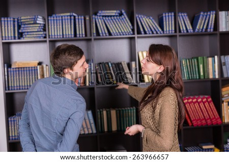 Sweet Young Couple Standing While Talking Beside Bookshelves at the Library - stock photo