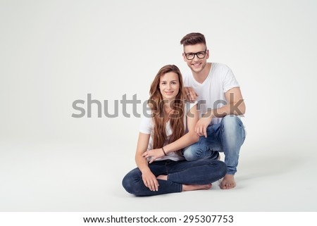 Sweet Young Couple Wearing Casual White Shirts and Blue Jeans Clothing, Smiling at the Camera on White Background with Copy Space. - stock photo