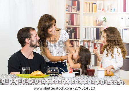 Sweet young family spending time together during breakfast - stock photo