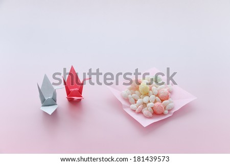 Sweetened rice-flour cakes and a folded?paper crane - stock photo