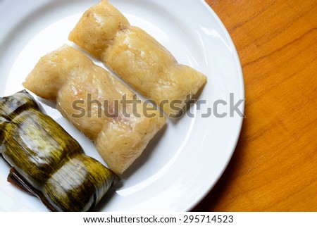 sweetmeat Thai dessert, Black Sticky Rice with Coconut Milk and babana, Grilled stuffed Glutinous rice wrapped in banana leaves - stock photo
