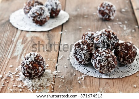 Sweets from figs and nuts in coconut flakes. Handmade. Vedic food. Healthy food. Natural product - stock photo