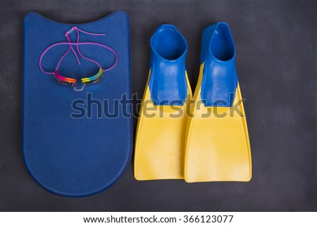 Swim fins, kick board and goggles on a blackboard or chalkboard for high school swim team background or competitive swim teams.  - stock photo