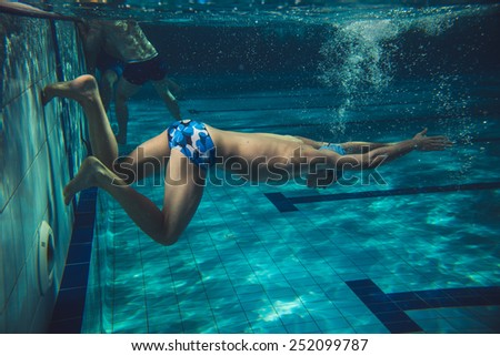 Swimmer in swimming pool.Underwater image.Grain effect added for artistic impression. - stock photo