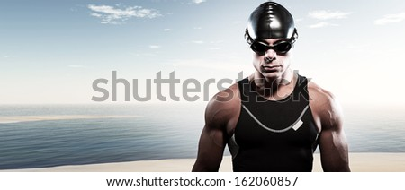 Swimmer triathlon muscled man with cap and glasses outdoor at a lake with blue cloudy sky. Extreme fitness sport. - stock photo
