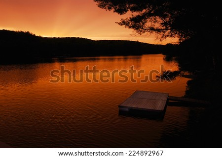 Swimming dock at sunset in a Canadian provincial park - stock photo
