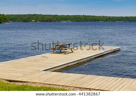 Swimming dock with table and a towel - stock photo