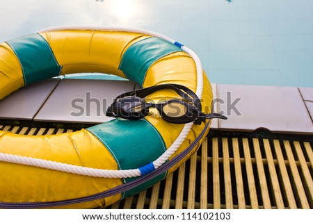 Swimming glasses on the life preserver floating - stock photo