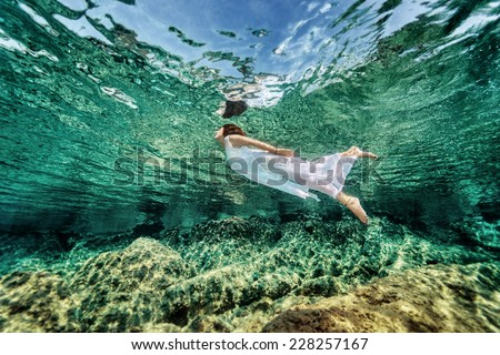 Swimming in transparent sea, emerges from clear sea, wearing fashionable white dress, luxury summer vacation, freedom and enjoyment concept - stock photo