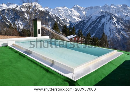 Swimming pool against snowy Alps. Switzerland - stock photo