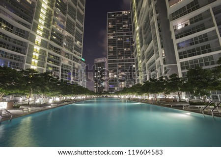 Swimming pool among high rise buildings by night - stock photo