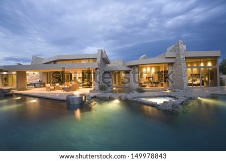 Swimming pool and illuminated modern house exterior against the sky - stock photo