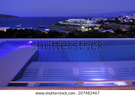 swimming pool and open air balcony in night illumination at the modern luxury hotel with Aegean Sea as background, Crete, Greece - stock photo