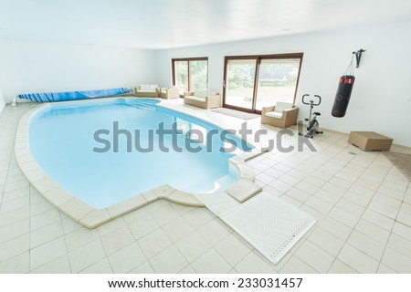 Swimming pool and sporty equipment in luxury villa - stock photo