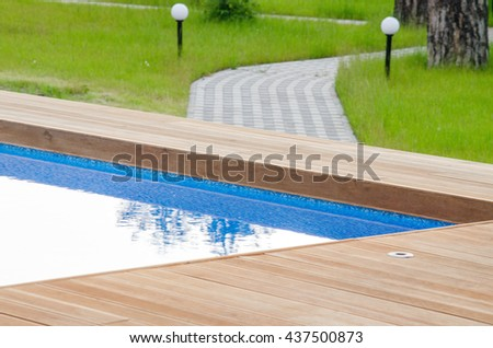 Swimming pool and wooden deck - stock photo