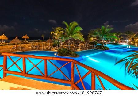 Swimming pool at luxury caribbean resort at night, dawn time. Bahia Principe, Riviera Maya, Mexico. - stock photo
