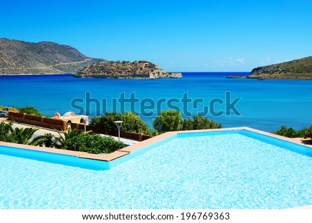 Swimming pool at luxury hotel with a view on Spinalonga Island, Crete, Greece - stock photo