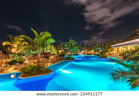 Swimming pool at promenade and restaurant at luxury caribbean resort at night, dawn time. Mexico. - stock photo