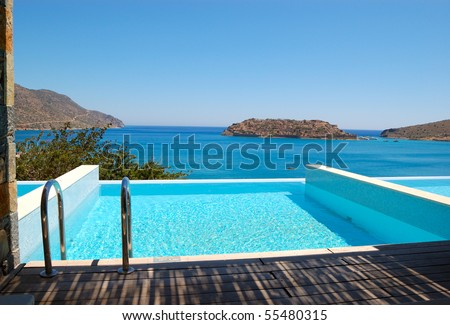 Swimming pool by luxury villa with a view on Spinalonga Island, Crete, Greece - stock photo