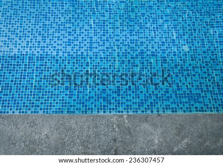 Swimming pool cement border with blue water texture - stock photo