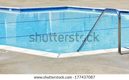 Swimming pool handle goes into the water. - stock photo