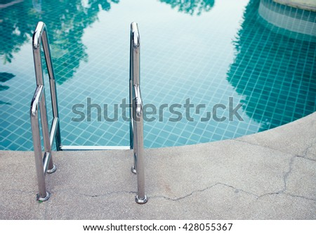 Swimming pool in curved shape with stairs.  - stock photo