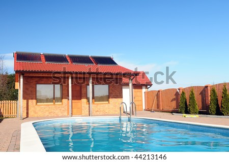 Swimming pool in front of small bungalow with solar panels on roof. - stock photo