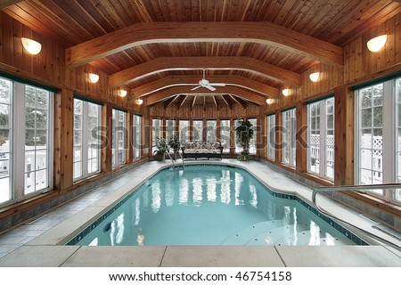Swimming pool in luxury home with wood ceiling beams - stock photo